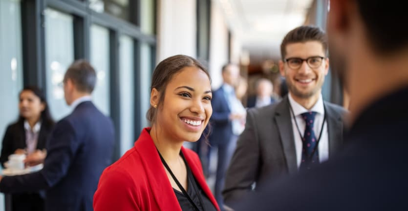 A young businesswoman in a red blazer smiles at a businessman at a professional networking event.