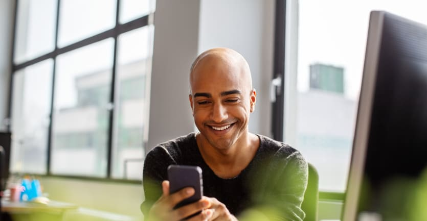 A young man happily checks his smart phone while sitting at his desk in a brightly lit office.