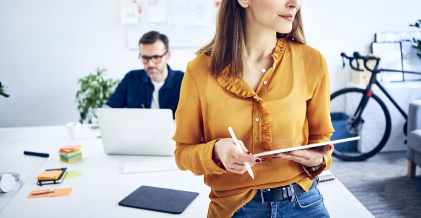 A woman in a mustard blouse french-tucked into a pair of skinny jeans leans against a desk in a brightly lit office, tablet computer in hand, as shecontemplatesabusiness decision.