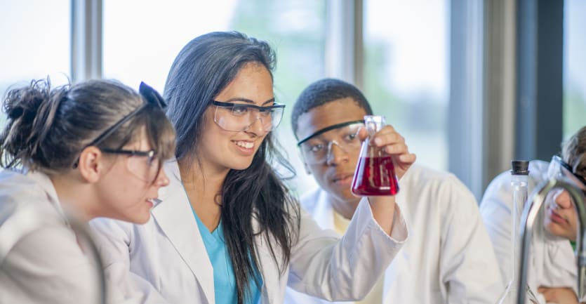 Three students in a chemistry lab observe a beaker filled with a red liquid.