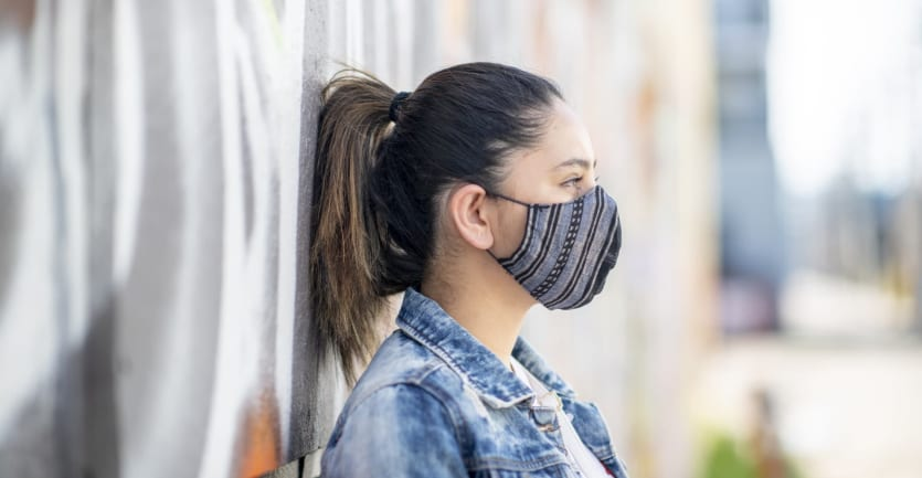 A college student wearing a jean jacket and face mask leans against a wall covered in graffiti.