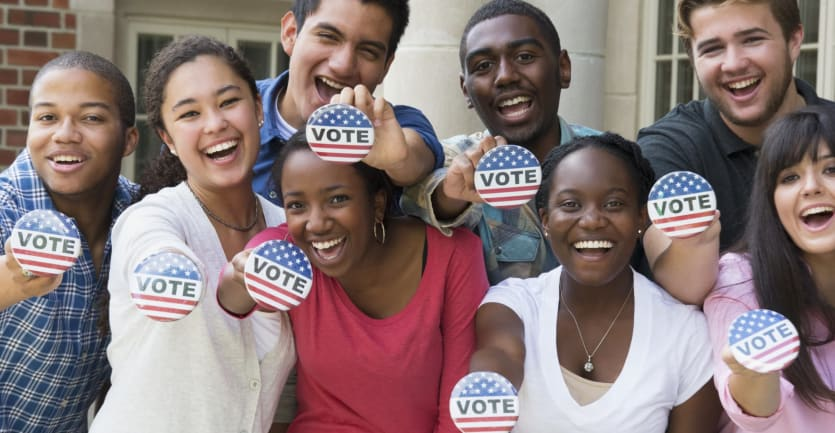 A group of smiling college students face the camera to show off their voting pins.