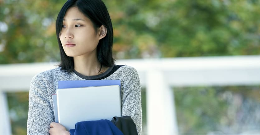 A young college student clutches her books to her chest while solemnly looking off in the distance.