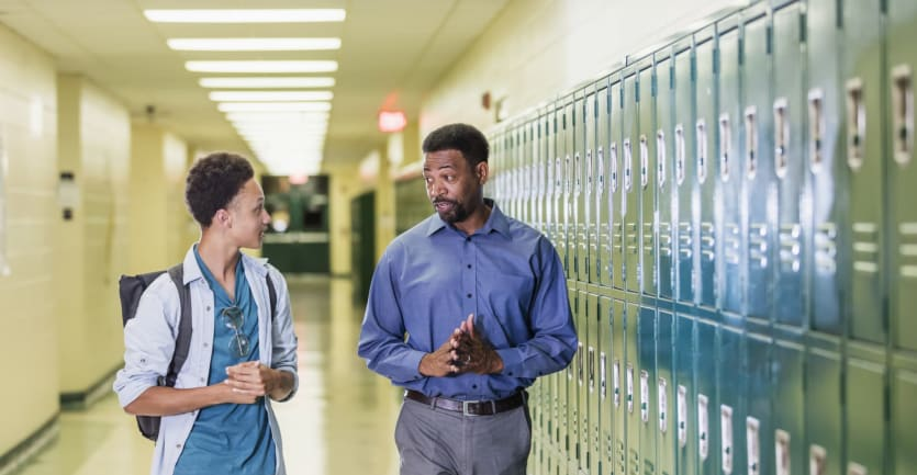 A high school counselor speaks with a student in a locker-lined hallway.