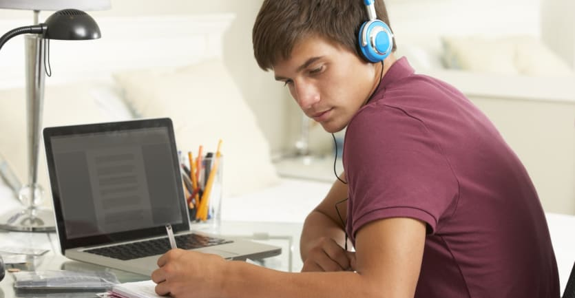 A teenage boy wearing a red T-shirt and blue headphones takes notes while studying in front of his laptop.