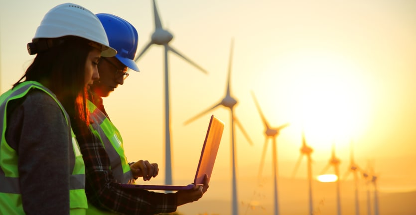 A pair of engineers in hard hats and yellow vests check out a laptop computer while the sun sets behind a row of wind turbines.