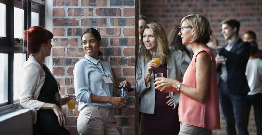 A group of smartly dressed women holding drinks chat while standing beneath a large window.