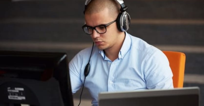 A man in a collared shirt, dark-framed glasses, and noise-canceling headphones sits working at a computer.