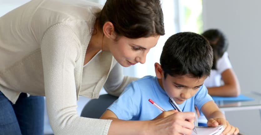 A teacher wearing jeans and a cream-colored cardigan leans over a student's desk to correct a piece of homework.