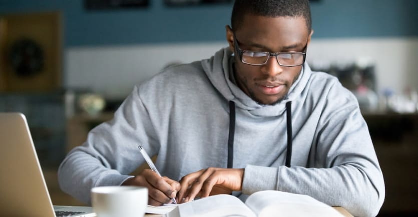 male student writing in notebook