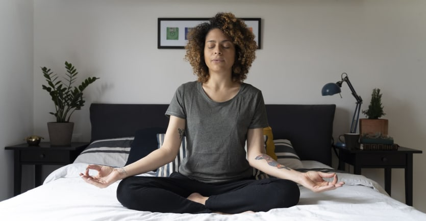 A woman sits cross-legged on her bed with her eyes closed deep in meditation.