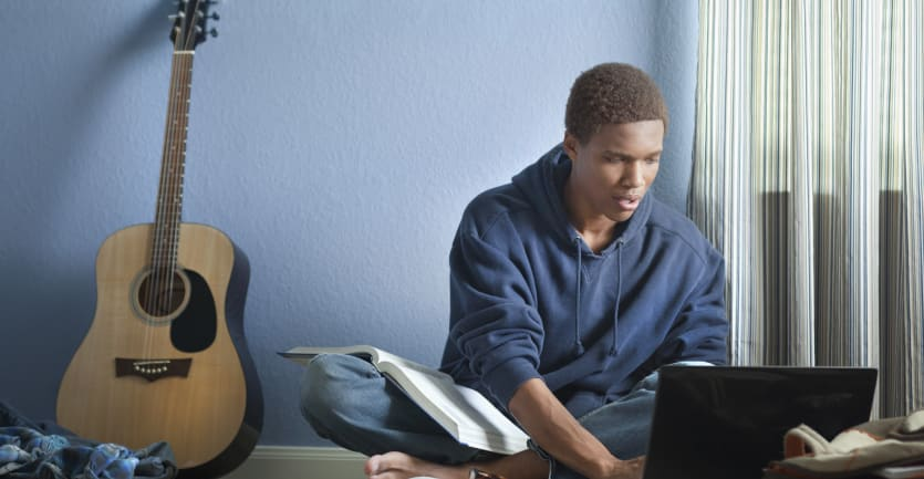 A young man in a hooded sweatshirt sits cross-legged on the floor, consulting an laptop before him and an open book in his lap.