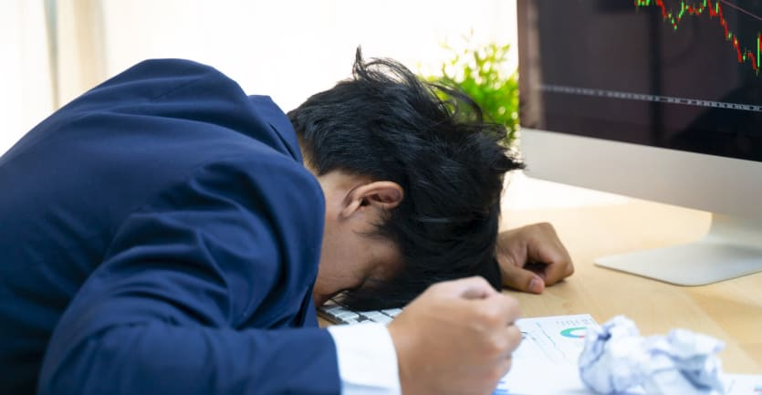 An anguished man in a suit clenches his fist at his desk as he lays his head down on his computer keyboard.