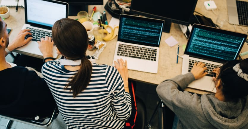 An overheaf shot of three developers consulting each others' laptops for an error in some code; their shared table is littered with a banana peel, coffee cups, and soda cans.