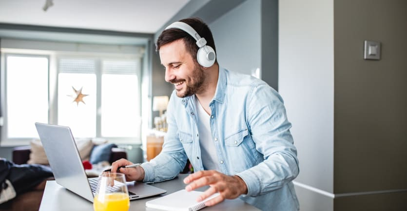 A man in a denim button-down shirt and over-ear headphones smiles as he looks at his laptop computer propped on his kitchen counter.