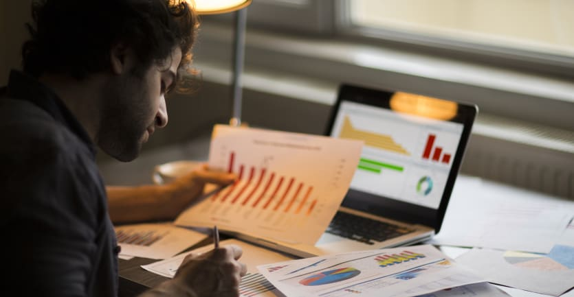 A man scribbles notes on printouts of graphs and charts sprawled across a busy desk.