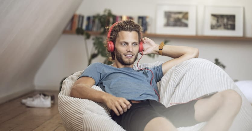 A man in shorts and a t-shirt lounges at home, listening to a podcast on his headphones while sprawled on a beanbag.