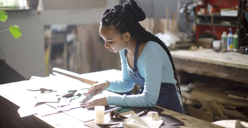 A young woman in long-sleeved t-shirt and apron carefully uses a utility knife to cut out materials on a large worktable.