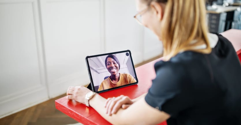 A young woman in a t-shirt and glasses holds a video call with a fellow student on her tablet computer.