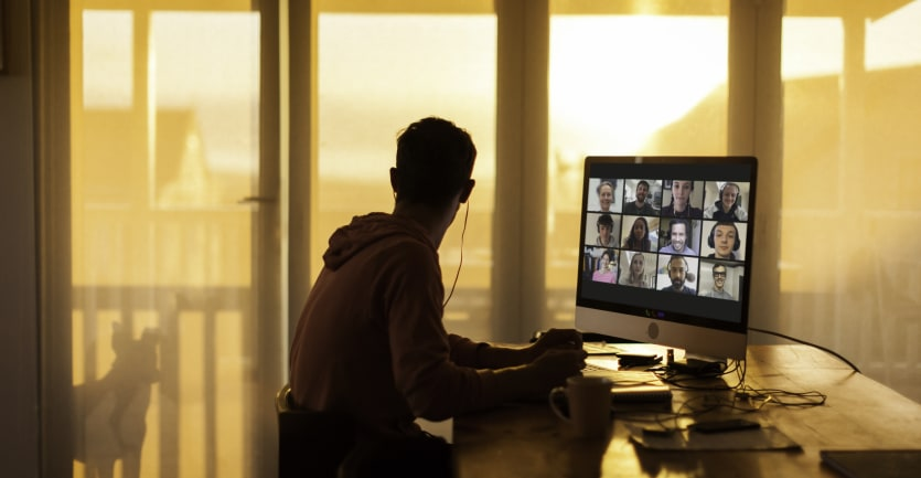 A man in a hoodie sweatshirt attends a virtual conference meeting on his desktop computer but turns his head to his balcony widnow, distracted by the silhouette of a dog.