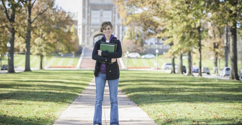 A woman in jeans, a hoodie, and an overcoat stands, smiling and holding several binders, in the middle of a college campus in the fall.