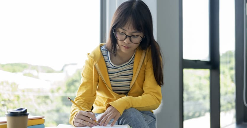 A woman in glasses and a brightly colored sweatshirt sits at a cafe table next to a floor-to-ceiling window and marks up a passage in a textbook.