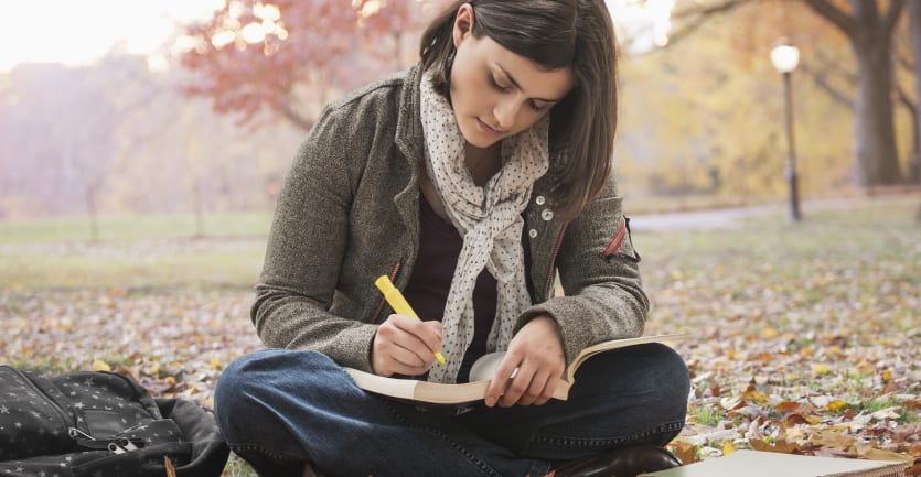 A woman wearing a jacket and scarf sits crosslegged on a foggy, leaf-strewn field on a college campus, highlighting a passage in a book.