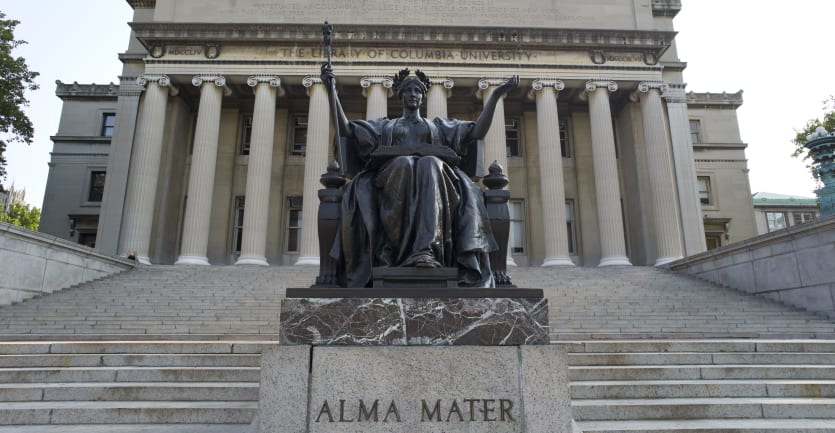 A statue of a woman with outstretched arms sits in front of the main library at Columbia University.