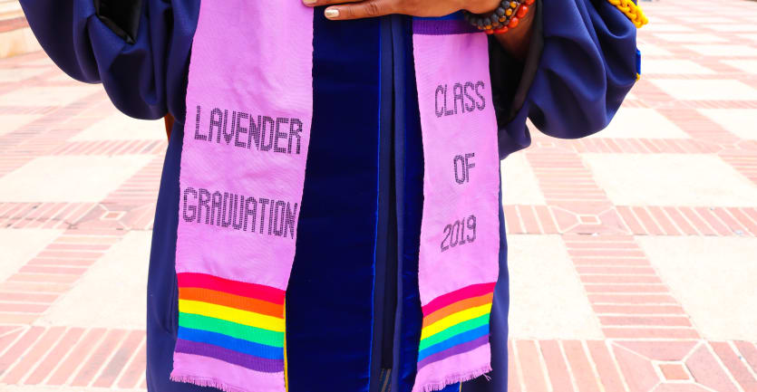 A college graduate stands outside wearing a graduation stole that reads 'Lavender Graduation Class of 2019.'