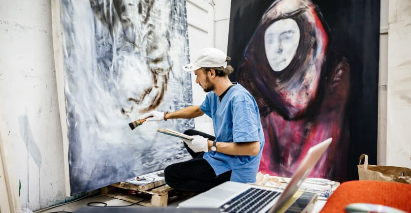 A young man wearing a white baseball cap and smock paints on a giant canvas in a room.