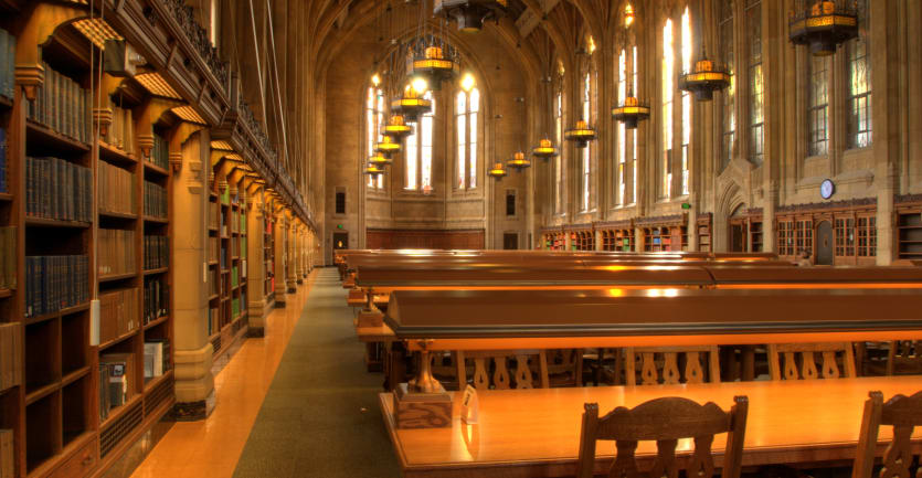 Rows of long tables sit empty in the long, Gothic vault of a university library.