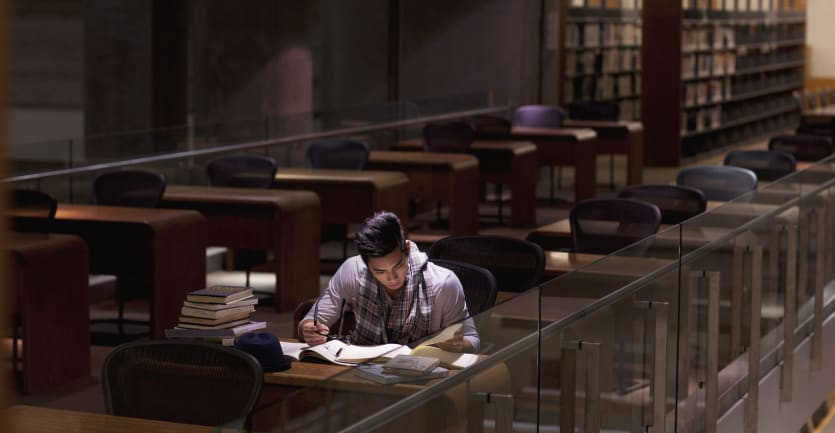 A young  man wearing a long-sleeved t-shirt and a scarf sits alone at a table piled high with books in a library room at night.