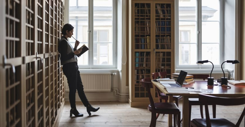 In a brightly lit room with tall windows and floor-to-ceiling bookcases, a smartly dressed woman ponders a question.