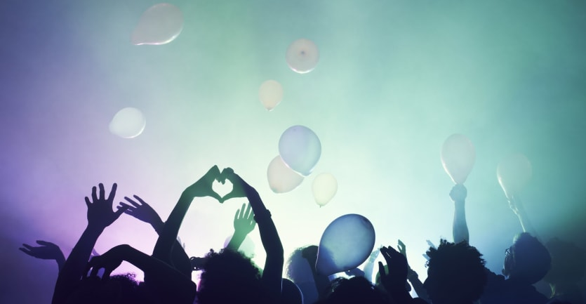 The silhouette of a crowd at a live concert is framed against smoke, lights, and balloons.