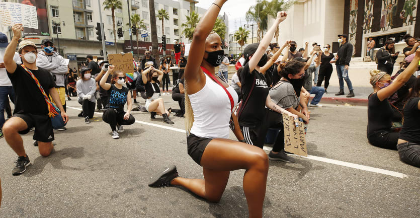 A large group of people made up of mostly college students protests on a street in Hollywood by taking a knee and raising their fists high in the air.