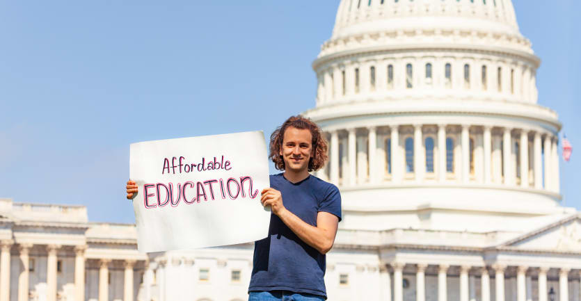 A college student in jeans and a t-shirt holds up a sign that reads Affordable Education while standing in front of the United States Capitol Building on a sunny day.