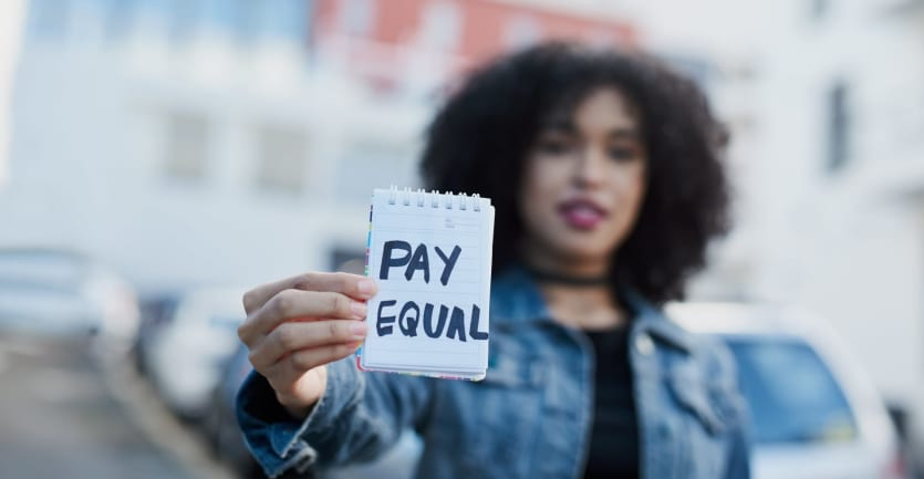 A woman in a dark t-shirt and denim jacket holds up a small reporter's notebook with the message PAY EQUAL scrawled in Sharpie.