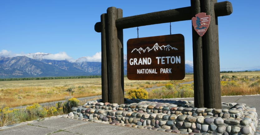 A large sign reading Grand Teton National Park stands against a serene backdrop of fields and distant mountains.