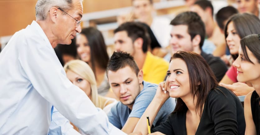 A middle-aged professor answers a smiling student's question in a crowded lecture hall.