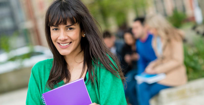 A young woman wearing a loose-fitting teal sweater and holding a spiral-bound notebook on a college campus smiles at the camera.