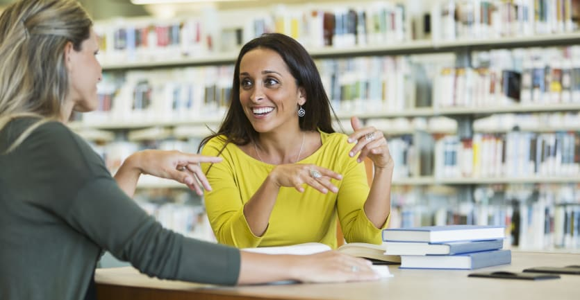 A young woman in a yellow blouse sit with her mentor at a tablke in the common area of an academic library.