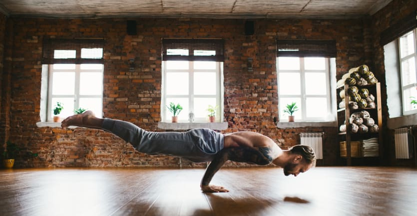 A shirtless man in sweatpants suspends himself from the floor using only his arms in a brightly lit yoga studio.