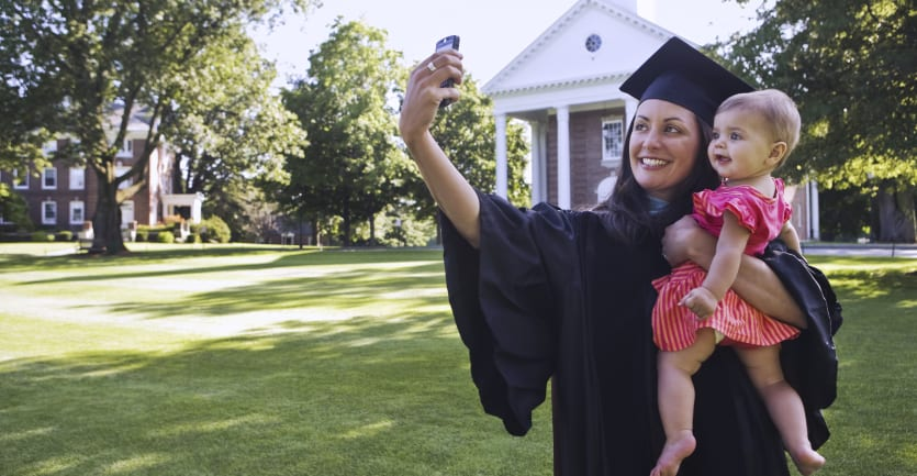 A woman in a graduation cap and gown standing on a college campus green smiles and takes a selfie while holding her infant child.