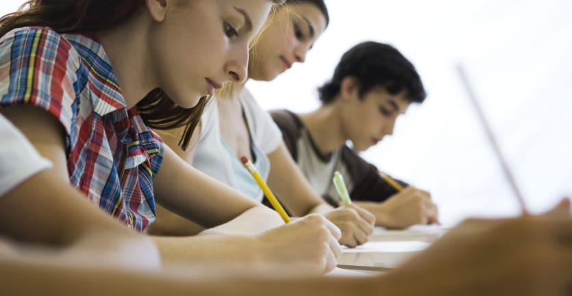 Several high school students take a test at their respective desks in a classroom.