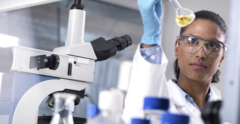 A woman wearing safety goggles, a white lab copat, and plastic gloves is framed by a microscope and assorted medical equipment as she examines a beaker filled with a mysterious fluid.