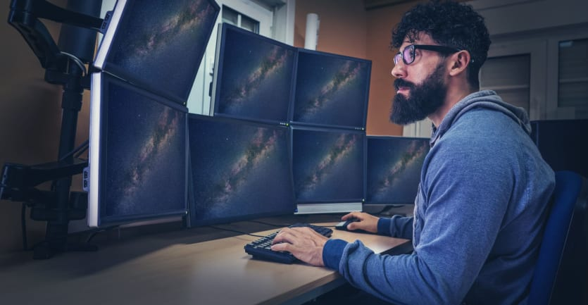 A bearded man wearing glasses and a hooded jacket sits at an array of computer monitors displaying photos of astronomical phenomena.