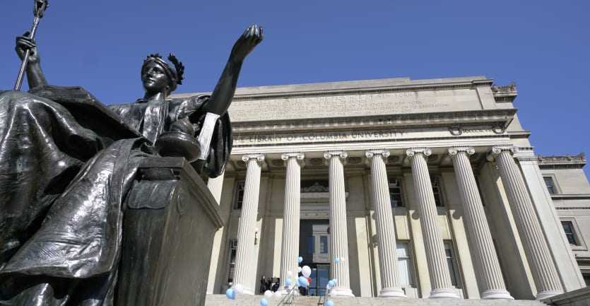 A bronze statue of a woman with her left arm outstretched sits in front of Columbia University's Low Library.