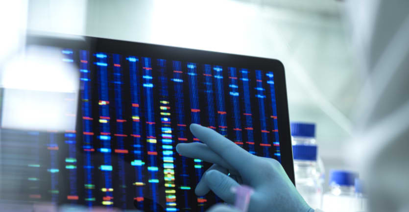 A researcher wearing a blue rubber glove touches a computer screen displaying color-coded genetic patterns.