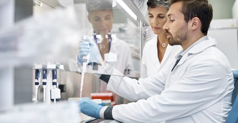 A female scientist stands beside a male colleague as he conducts cancer research in a laboratory.