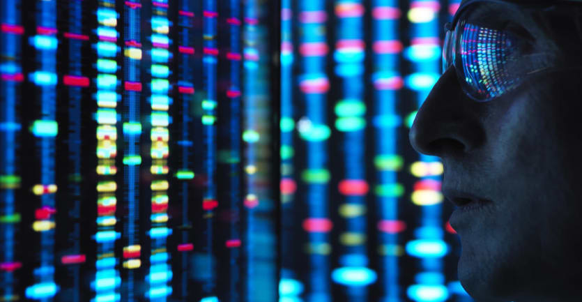 A scientist gazes at a screen displaying color-coded genetic patterns, the images reflecting off his glasses.